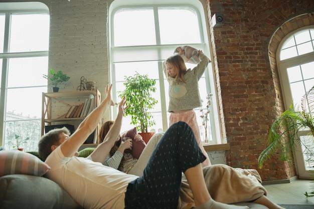 Rindo. família passando bons momentos juntos em casa, parece feliz e alegre. mãe, pai e filha se divertindo, lutando com almofadas. união, conforto do lar, amor, conceito de relações.
