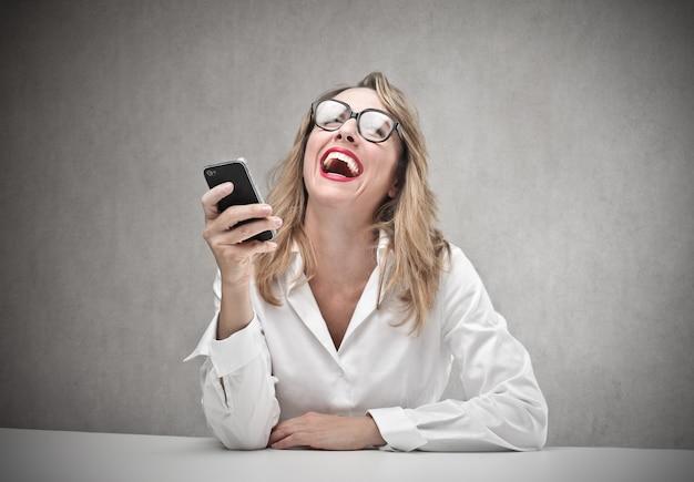 Rindo feliz mulher segurando um smartphone