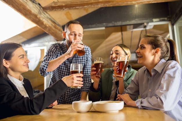 Rindo. felizes colegas de trabalho comemorando o evento corporativo após um dia tenso de trabalho. pareça encantado, amigável, alegre. bebendo cerveja. conceito de cultura de escritório, trabalho em equipe, amizade, feriados, fim de semana.