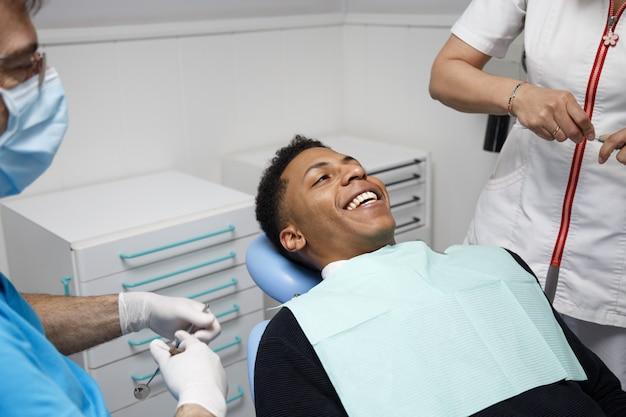 Rindo homem afro-americano sentado na cadeira do dentista na clínica e se preparando para o procedimento com a enfermeira.