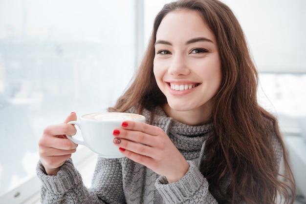 Rindo jovem bebendo café.