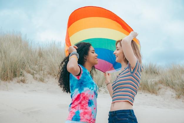 Rindo jovem casal de lésbicas conversando e movendo a bandeira do orgulho gay em uma praia arenosa - imagem stock