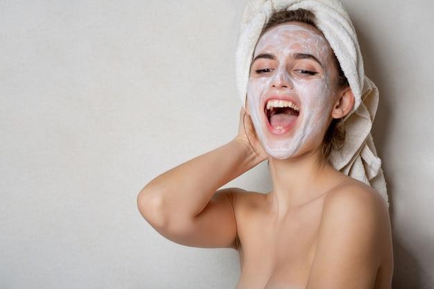 Rindo jovem com toalha de banho na cabeça usando máscara hidratante no rosto. conceito de cuidados pessoais em casa. espaço para texto