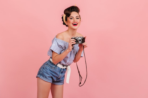 Rindo jovem em shorts jeans, tirando fotos. foto de estúdio de garota pin-up com câmera isolada no fundo rosa.