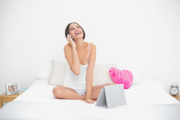 Rindo jovem modelo de cabelos castanhos em pijama branco fazendo um telefonema