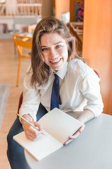 Rindo menina adolescente fazendo anotações no bloco de notas