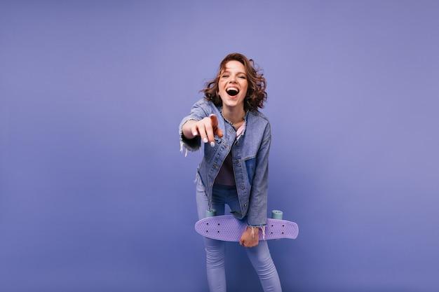 Rindo menina bem-humorada arrepiante. mulher animada na moda com o skate se divertindo.