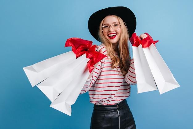 Rindo menina caucasiana em copos segurando sacolas de compras. vista frontal da encantadora senhora shopaholic isolada sobre fundo azul.