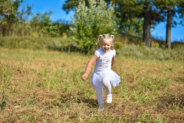 Rindo menina de vestido branco correndo pelo campo em uma tarde ensolarada