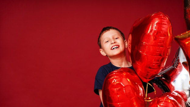 Rindo menino, coração de várias cores, balões estrela para aniversário