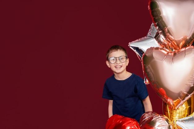Rindo menino de óculos, coração de cor diferente, estrela balões para aniversário