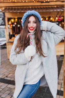 Rindo modelo feminino com cabelo castanho escuro, comendo doces de natal em um dia frio. retrato de alegre menina morena europeia de casaco cinza e luvas brancas, posando com pirulito na manhã de inverno.