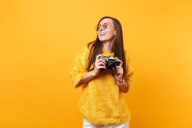 Rindo muito jovem com suéter de pele e óculos de coração segurando a câmera fotográfica vintage retrô isolada em fundo amarelo brilhante. conceito de estilo de vida de emoções sinceras de pessoas. área de publicidade.