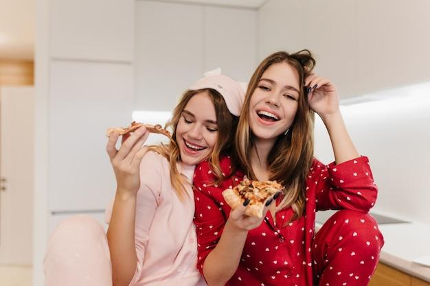 Rindo mulher europeia em pijamas fofa, passando a manhã com a irmã na máscara. senhoras muito brancas comendo pizza de queijo com prazer.