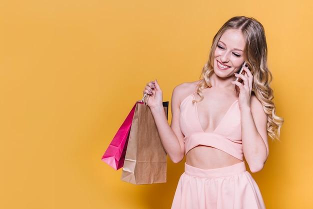 Rindo mulher falando no telefone enquanto fazia compras