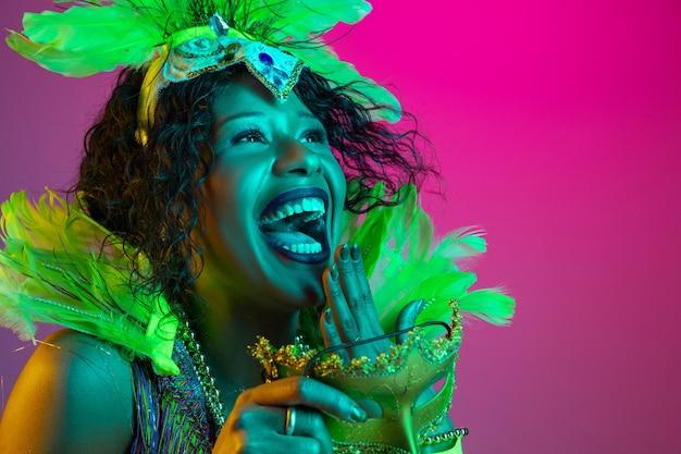 Rindo. mulher jovem e bonita no carnaval, elegante traje de máscaras com penas dançando na parede gradiente em neon. conceito de celebração de feriados, tempo festivo, dança, festa, diversão.