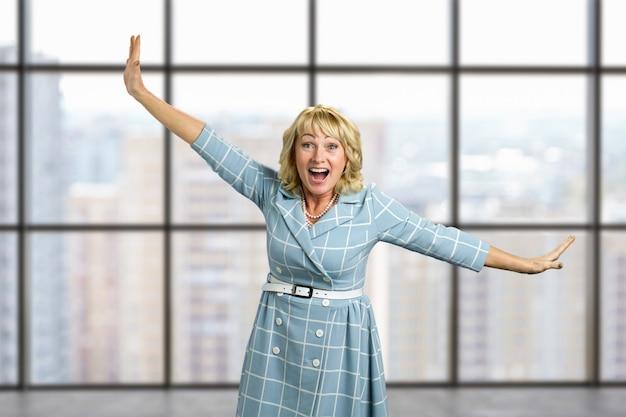 Rindo mulher madura na janela do escritório. mulher de pele branca rindo, esticando os braços na diagonal. senhora idosa alegre posando com esticando as mãos no escritório.