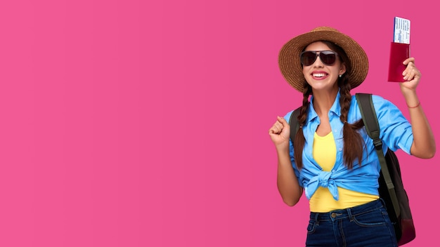 Rindo mulheres turistas em roupas casuais, com bilhetes de embarque e documentos. aluno feliz com chapéu de palha e mochila