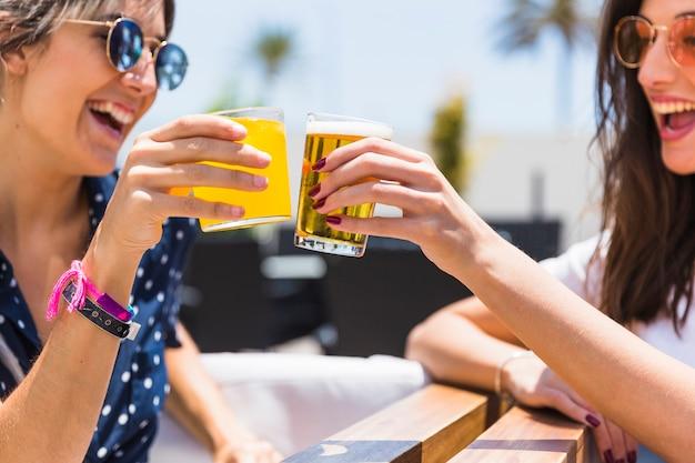 Rindo namoradas tilintar de copos com suco