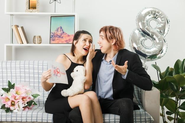 Rindo, olhando um para o outro, jovem casal no dia da mulher feliz com o ursinho de pelúcia e um cartão de felicitações sentado no sofá na sala de estar