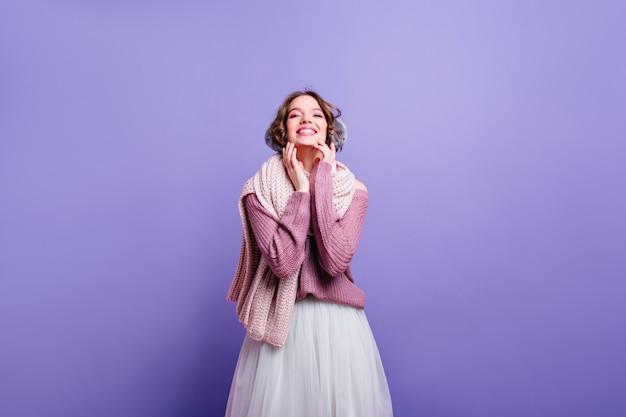 Rindo senhora caucasiana em acessórios de inverno, desfrutando da sessão de fotos. magnífica garota branca com saia vintage exuberante, posando na parede roxa.