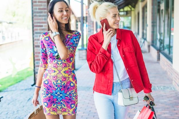 Rindo senhoras com sacolas de compras na rua comercial