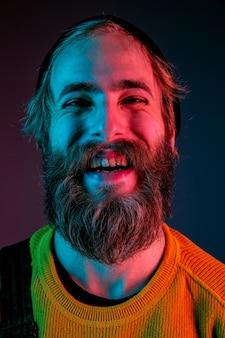 Rindo, sorrindo, de perto. retrato do homem caucasiano em fundo gradiente de estúdio em luz de néon. lindo modelo masculino com estilo hippie. conceito de emoções humanas, expressão facial, vendas, anúncio.
