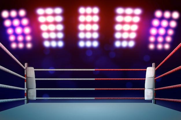Ringue de boxe com iluminação por holofotes.