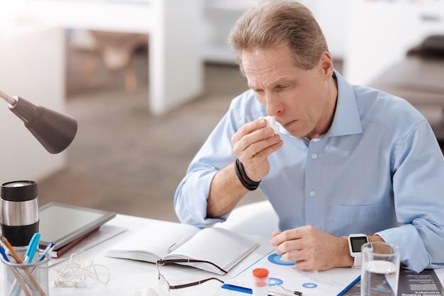 Rinite terrível. homem frustrado vestindo camisa azul, franzindo a testa enquanto pressiona os lábios