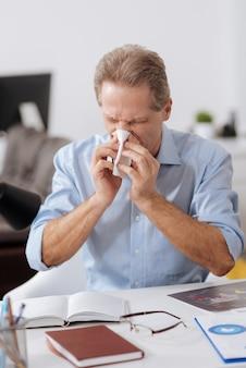 Rinite terrível. trabalhador de escritório perturbado vestindo camisa azul fechando os olhos enquanto assoa o nariz