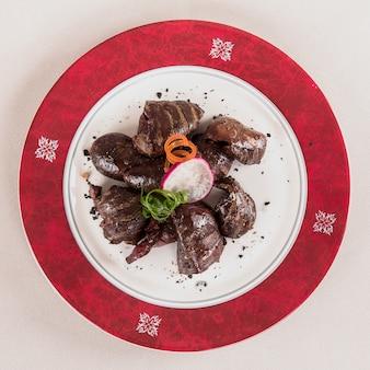 Rins de porco grelhado delicioso, decorado com folhas vermelhas e verdes