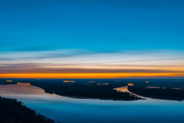 Rio bonito com grande ilha com árvores sob o céu antes do amanhecer.