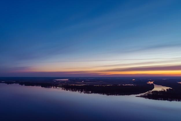 Rio bonito com grande ilha com árvores sob o céu antes do amanhecer