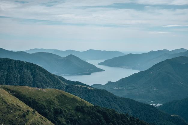 Rio cercado por colinas cobertas de florestas e nevoeiro sob o céu nublado e luz solar