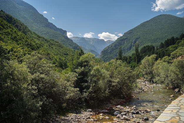 Rio cercado por colinas cobertas de vegetação sob um céu nublado e luz do sol