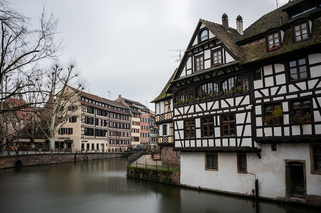 Rio cercado por edifícios coloridos e vegetação sob um céu nublado em estrasburgo, na frança