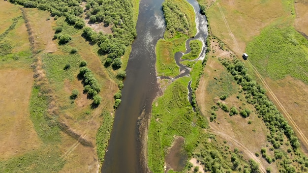 Rio cercado por prados e árvores