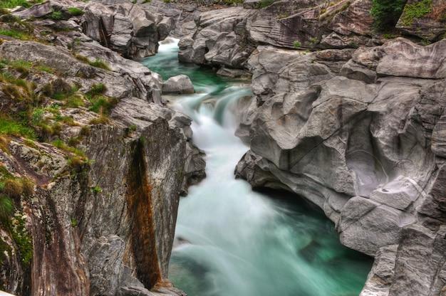 Rio cercado por rochas cobertas de musgos no valle verzasca, na suíça