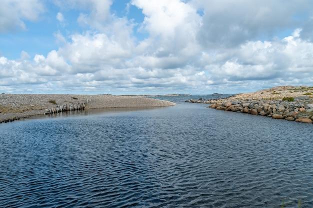 Rio cercado por rochas sob a luz do sol e céu nublado durante o dia