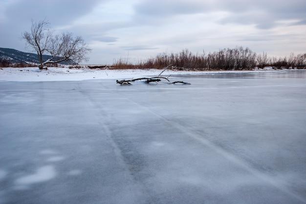Rio com água congelada e trilhas antigas de carro