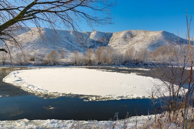 Rio congelando em margens montanhosas com grandes blocos de gelo