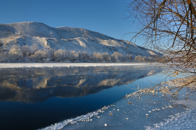 Rio congelando nas margens montanhosas e grandes blocos de gelo