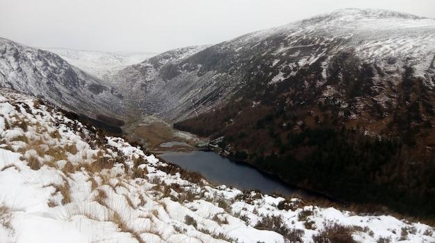 Rio correndo pela montanha coberto de neve