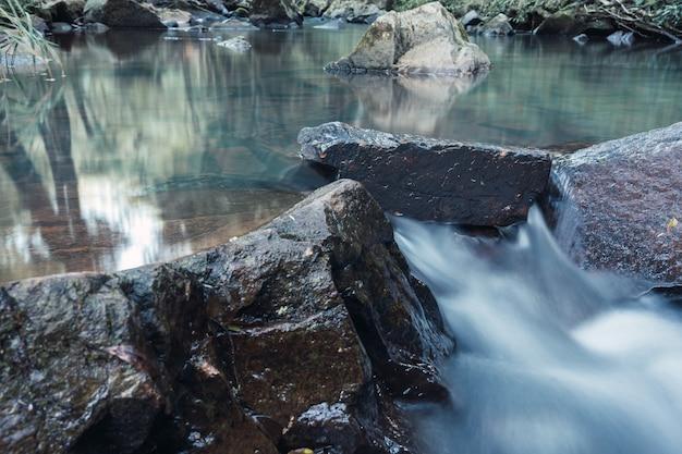 Rio de água cristalina que corre entre as rochas.