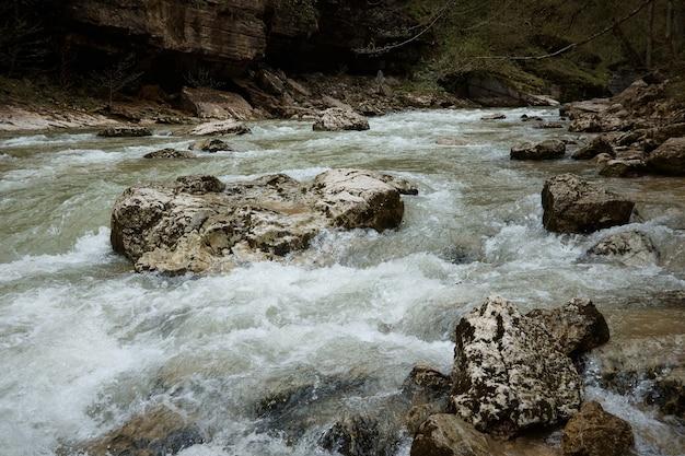 Rio de montanha com ondas violentas, rochas e rochas no rio, águas agitadas, paisagem
