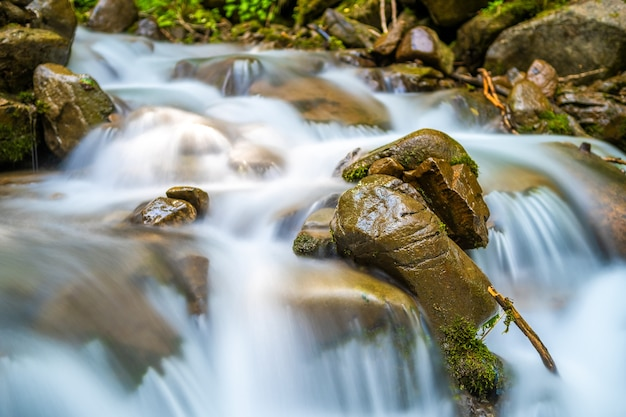 Rio de montanha com pequena cachoeira com águas cristalinas turquesa caindo entre pedregulhos molhados com espuma branca espessa.
