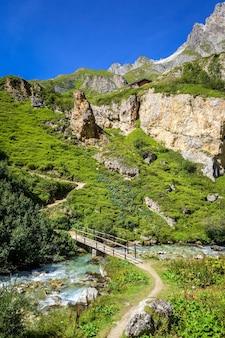 Rio de montanha e ponte de madeira no vale alpino de vanoise
