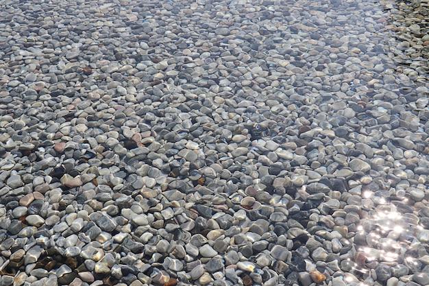 Rio de pedra sob fundo de textura de águas claras, close-up da superfície da rocha