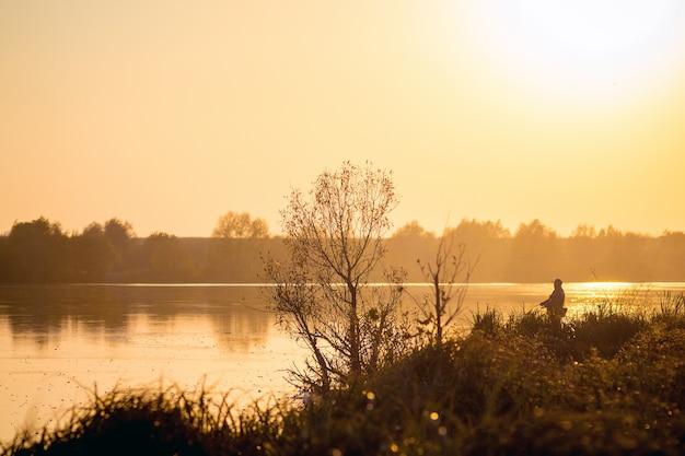 Rio e pescador na costa durante o pôr do sol_