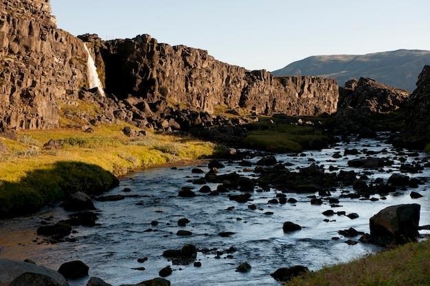 Rio em um vale iluminado pelo sol verde, uma cachoeira sobre o penhasco acidentado